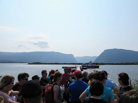 Western Brook Pond, Newfoundland, Canada - July 22nd, 2014:  A crowd of tourists waiting for the tour boat to visit the fjords of the Western brook pond in Gros Morne National Park, Newfoundland.