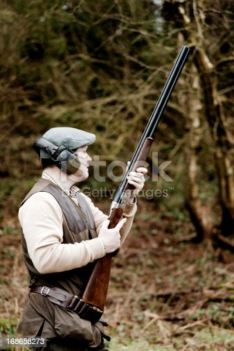 A man dressed in country clothing waits quietly at the edge of a wood for a bird to fly, Devon, UK