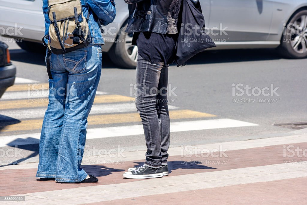 waiting women at the pedestrian crossing and car traffic stock photo