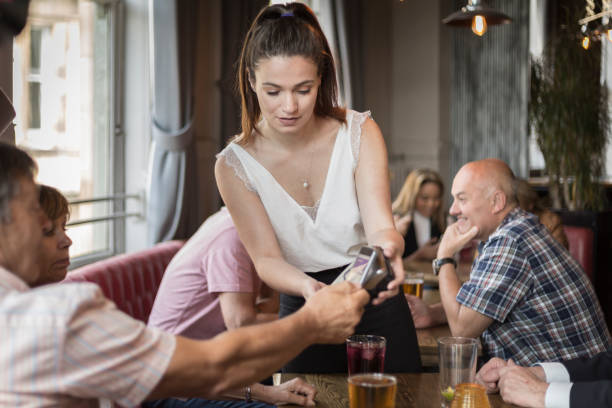 Waitress accepting contactless payment in cafe bar stock photo