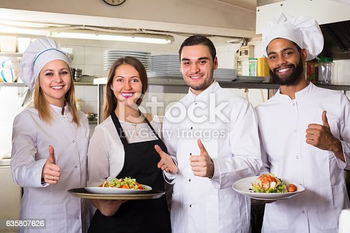 istock Waitress and cooking team in restaurant 635807626