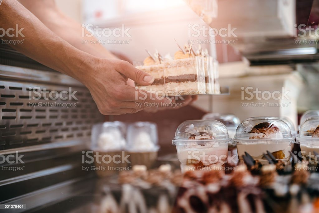 Waitress arranging cakes - Photo