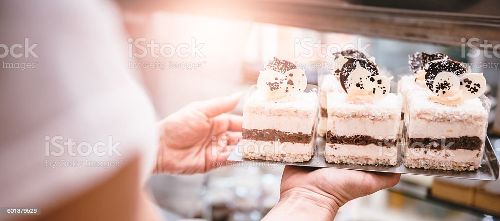 Waitress arranging cakes stock photo