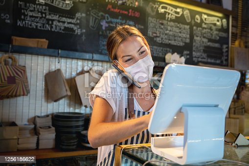 Waitress working at a restaurant getting a delivery order on the phone while wearing a facemask - COVID-19 lifestyle concepts