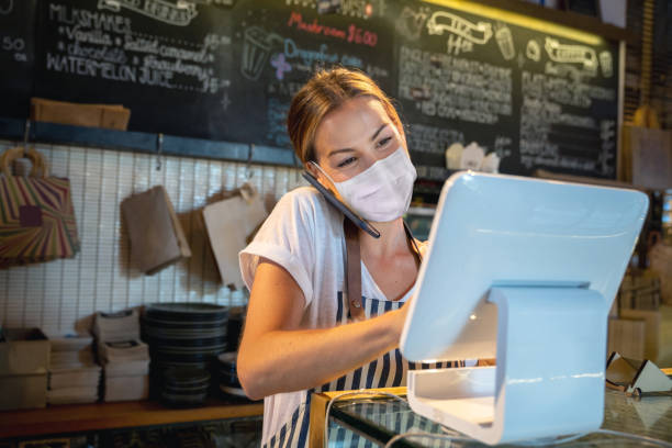 Waitress at a restaurant getting a delivery order on the phone and wearing a facemask stock photo