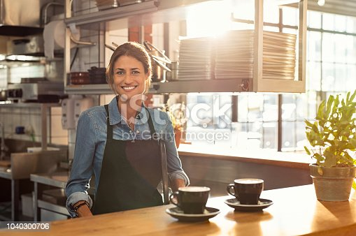 Smiling waitress wearing black apron standing behind counter in cafeteria and looking at camera. Mature woman serving two cups of hot coffee to customer in cafeteria. Small business and entrepreneur concept.