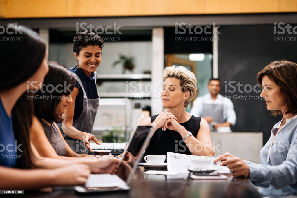Waitress bringing coffee to the table stock photo
