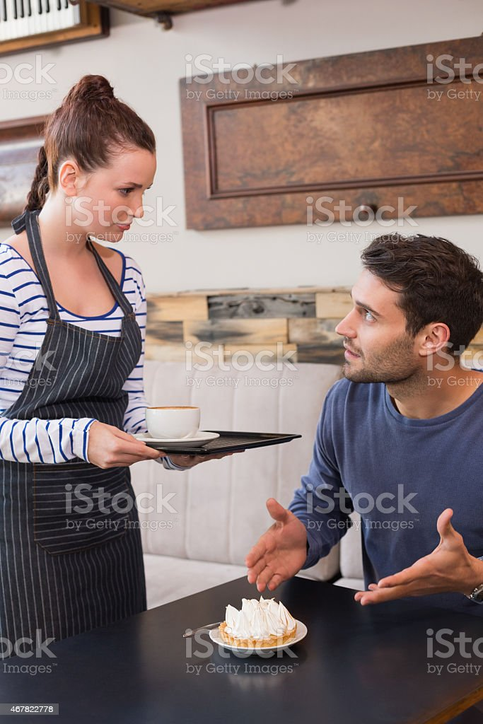 Waitress bringing man coffee and a tart stock photo