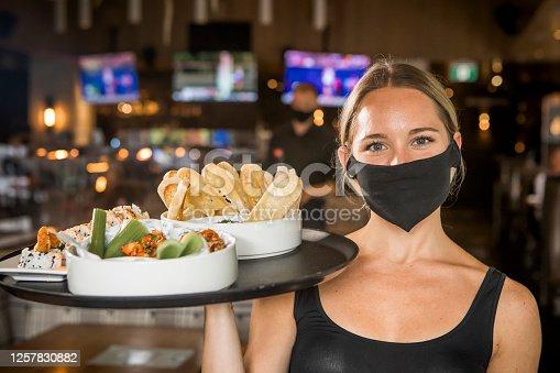 Waitress looking at camera, ready to serve customers.