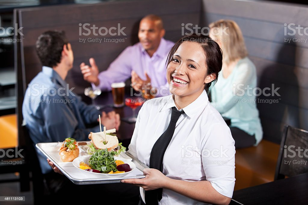 Waitress carrying tray with food stock photo