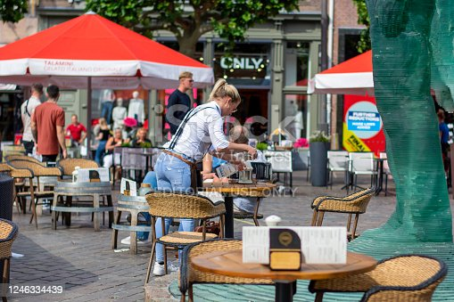 Waitress cleans a table on restaurant terrace with disinfectant alcohol spray. The terraces in The Netherlands were allowed to open again on 1 June, guidelines and rules must be adhered to. Zwolle, The Netherlands