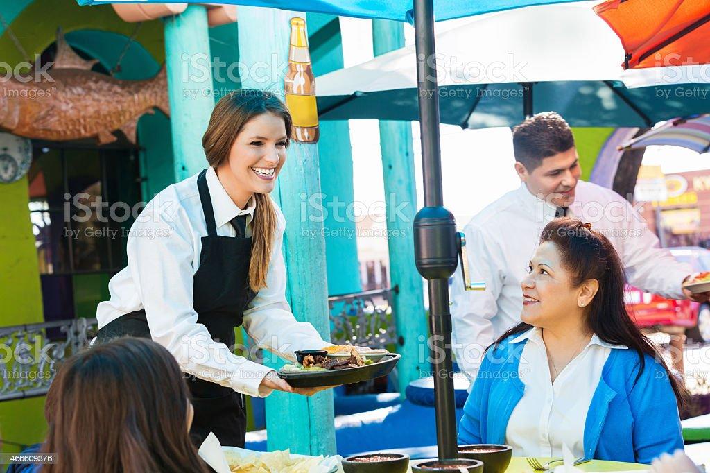 Waitress delivering fajitas to customer at Tex-Mex restaurant stock photo