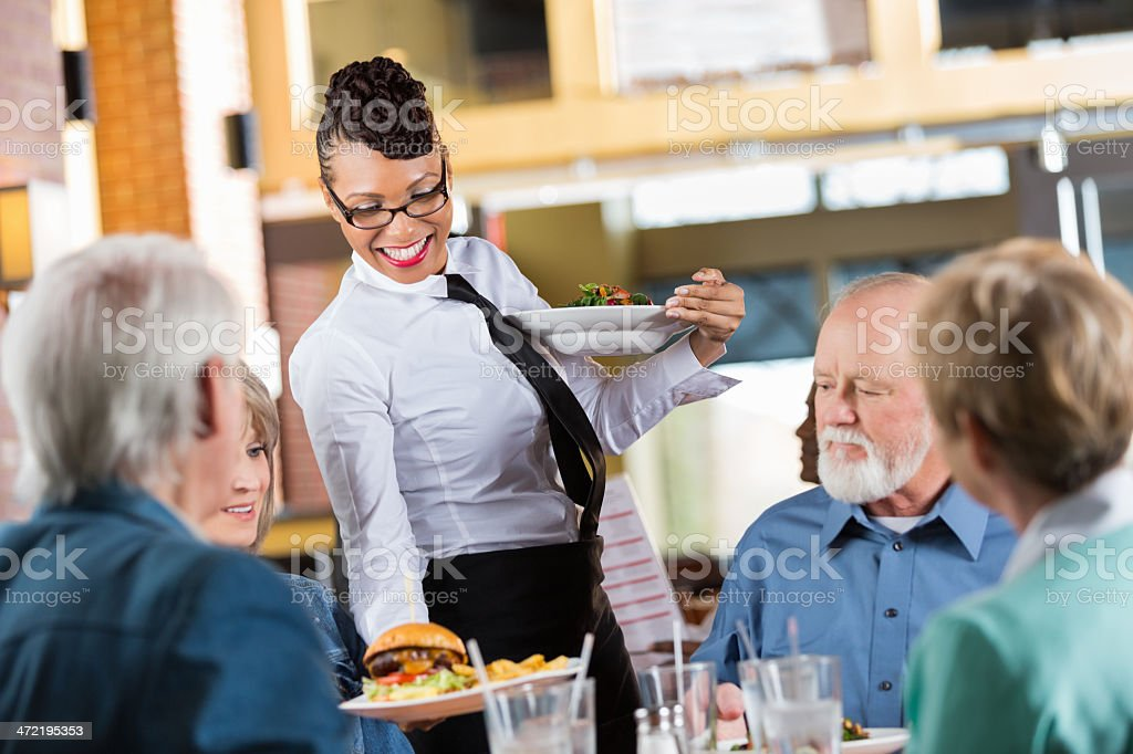 Waitress delivering food to customers' table in modern restaurant stock photo