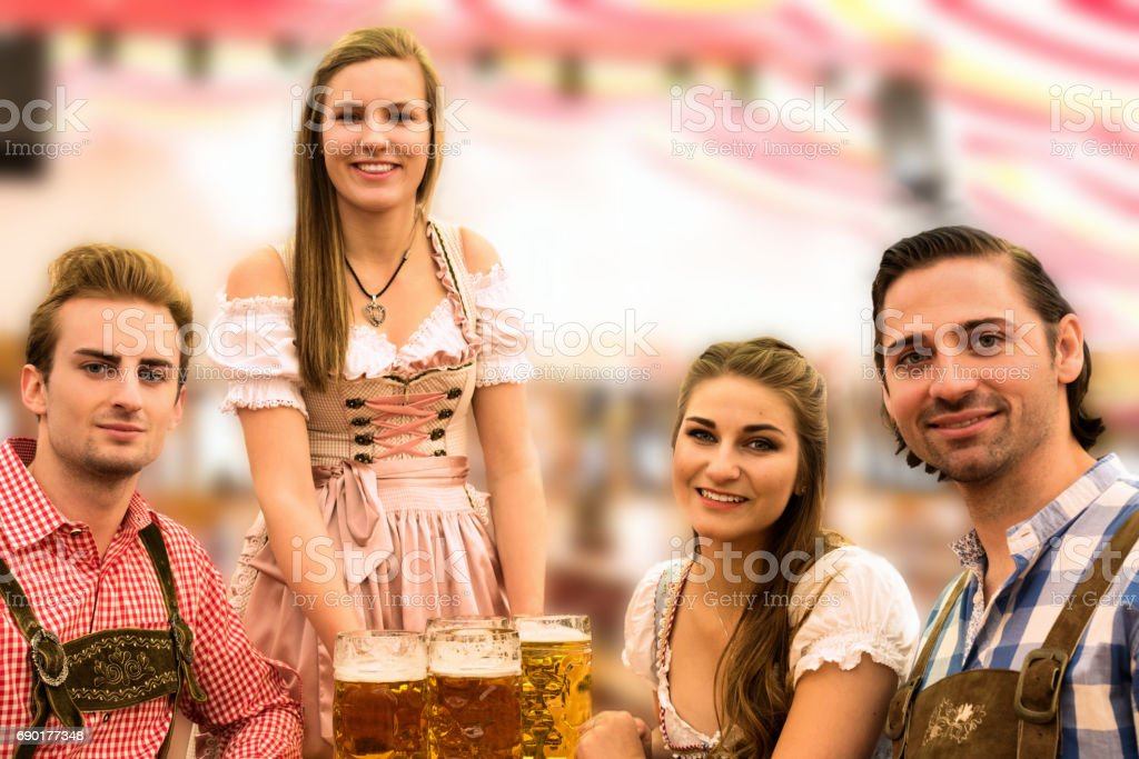 Waitress delivers beers in tent with happy visitors in a beer tent at Munich Oktoberfest – Foto