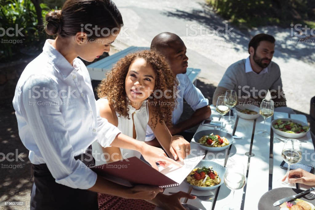 Waitress discussing the menu with woman in the restaurant stock photo