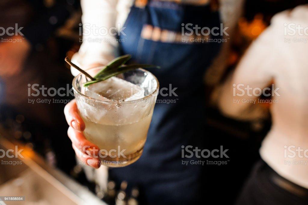 Garçonete vestida com uma camisa branca e avental azul, segurando um copo com bebida gelada - foto de acervo