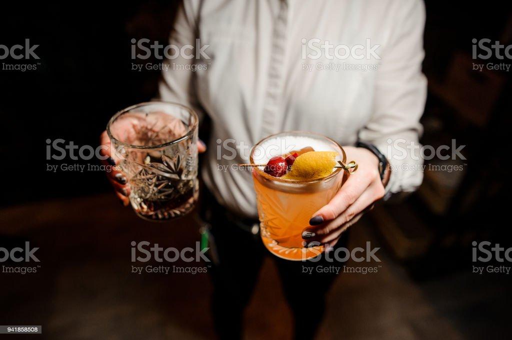 Garçonete vestida com uma camisa branca segurando copos com bebidas - foto de acervo