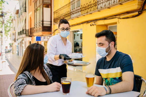 Waitress from a bar in Spain serves food and drinks to customers on her terrace. Everyone wears a mask to protect themselves from contagion. Phase one of the de-escalation.