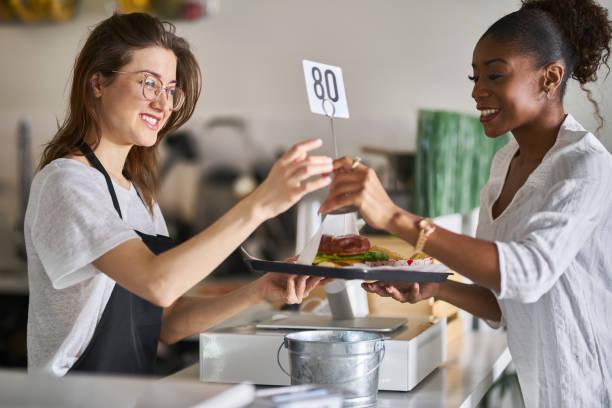 waitress handing order of food on tray to customer stock photo