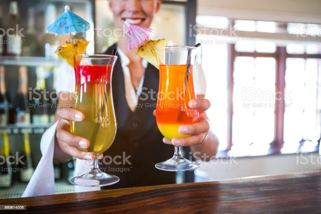 Waitress handing over cocktails royalty-free stock photo