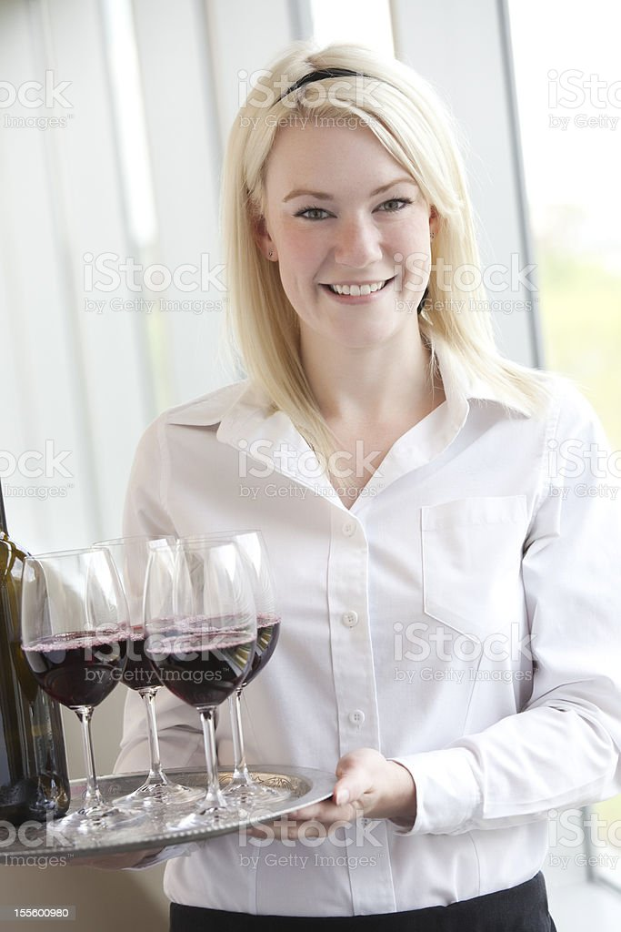 A waitress holding a tray of glasses of red wine royalty-free stock photo