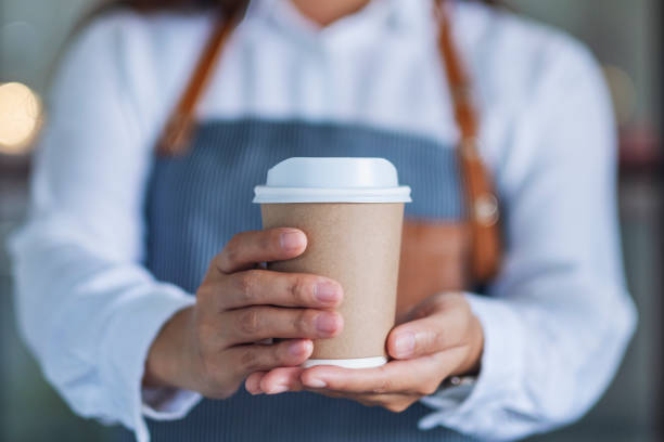 Eine Kellnerin hält und serviert eine Papiertasse heißen Kaffee – Foto