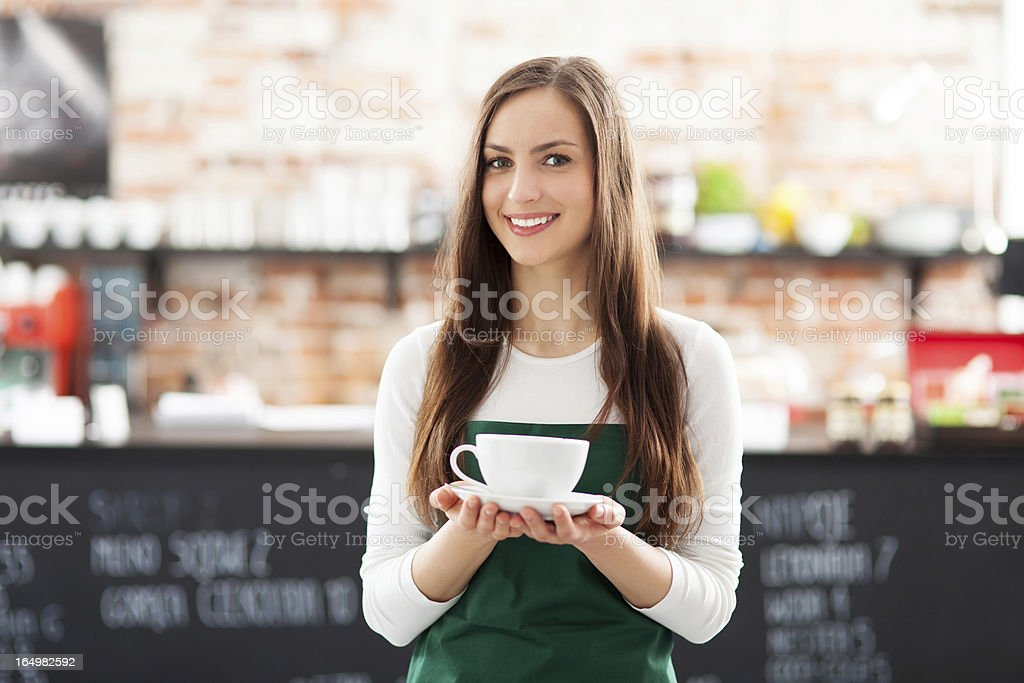 Waitress holding cup of coffee in cafe stock photo