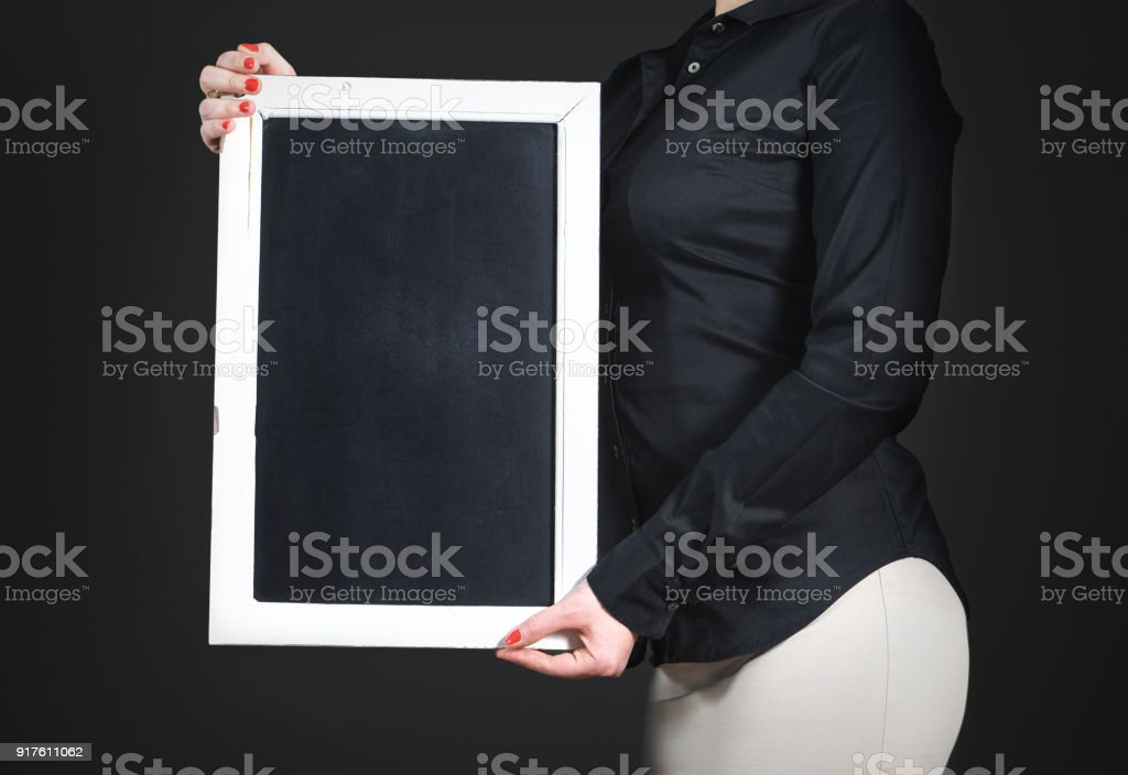 Waitress holding empty chalkboard. Young professional woman in black shirt with blank blackboard. Negative copy space for restaurant menu, cafe specials or happy hour deals in a bar. stock photo