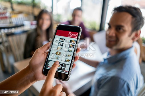 Waitress holding online menu on smart phone at a restaurant - small business using technology. *Design on screen was made from scratch by us.*