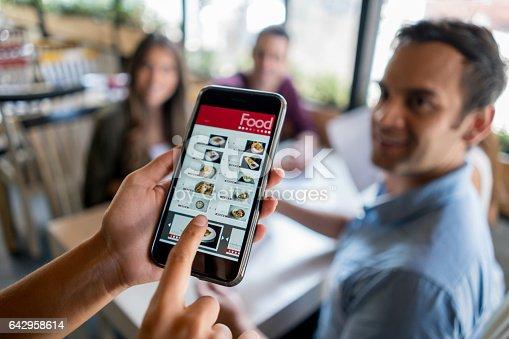 istock Waitress holding online menu on a smart phone 642958614