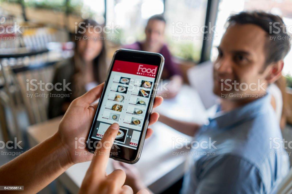 Kellnerin mit Online-Menü auf einem Smartphone – Foto