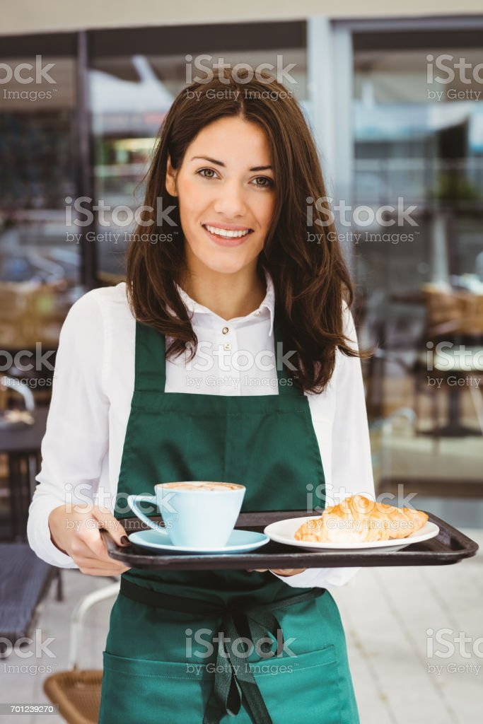 Waitress holding tray with coffee and croissant stock photo