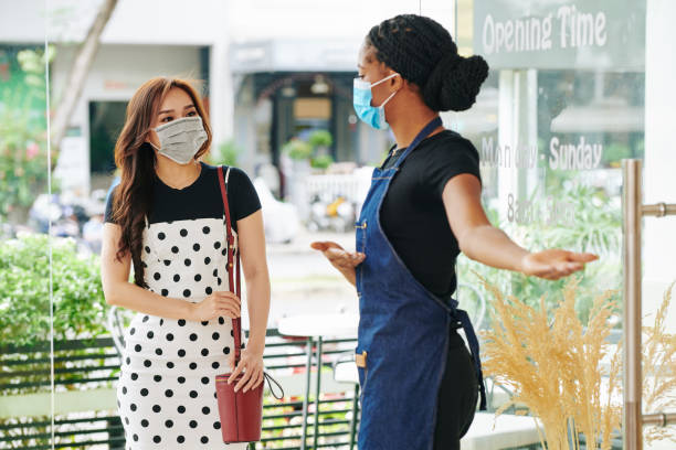Waitress in medical mask inviting customer stock photo