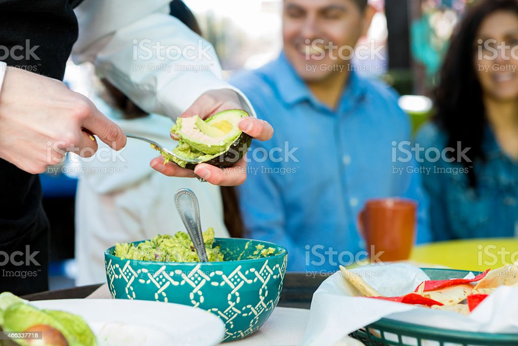 Waitress making table side guacamole for customers in restaurant stock photo