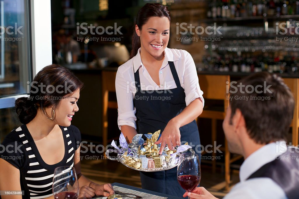 Waitress offering diners dessert tray stock photo