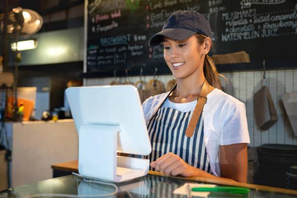 kellnerin, die erteilung des auftrages auf dem computer in einem restaurant - legere arbeitskleidung stock-fotos und bilder