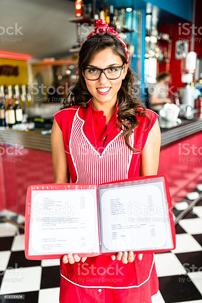 waitress posing at the bar counter with the menu open stock photo