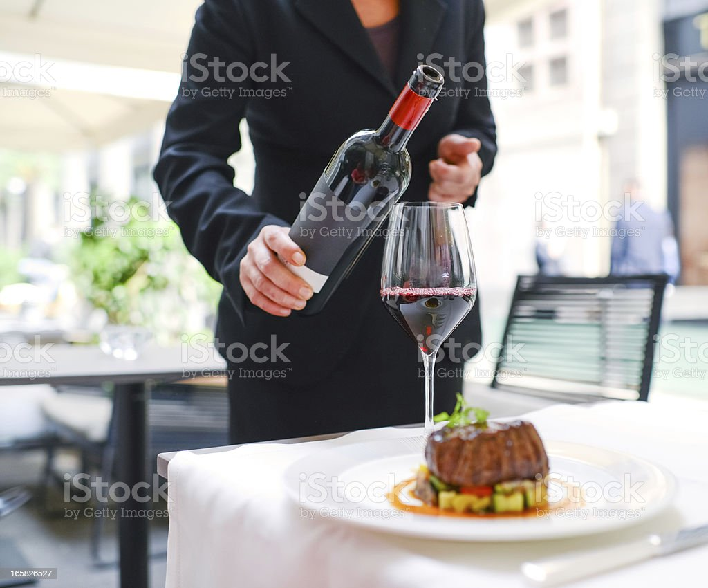 Waitress  pouring wine in glass stock photo