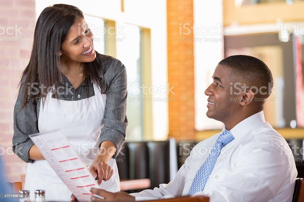 Waitress recommending menu item to customer in modern restaurant stock photo