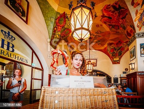 Munich, Germany - July 29, 2018: Young attractive waitress sells giants pretzels at the iconic Hofbrauhaus beer hall in Munich, Germany - ultra wide angle