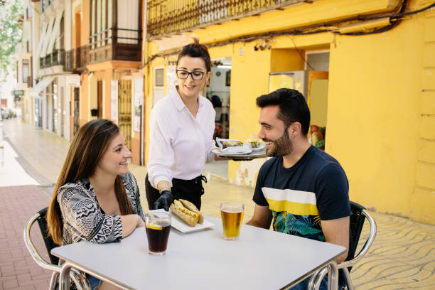 Waitress serves food to two young people on the terrace of a bar in Spain.