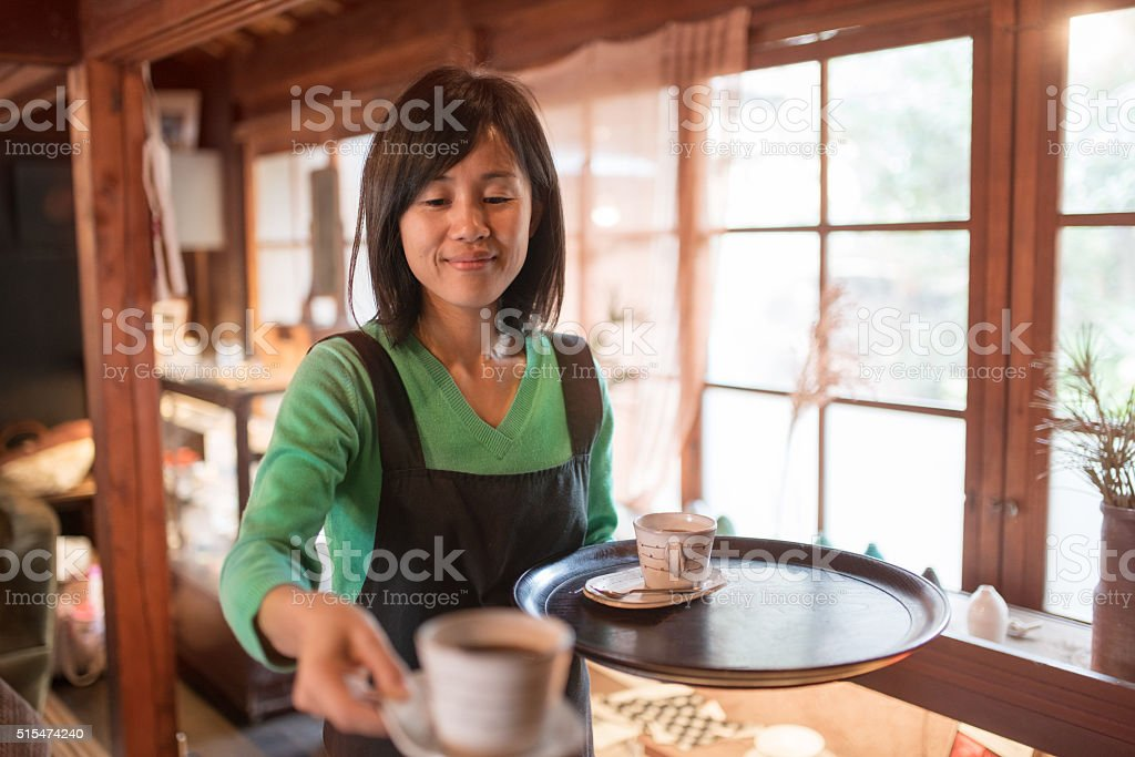Waitress serving a cup of coffee stock photo
