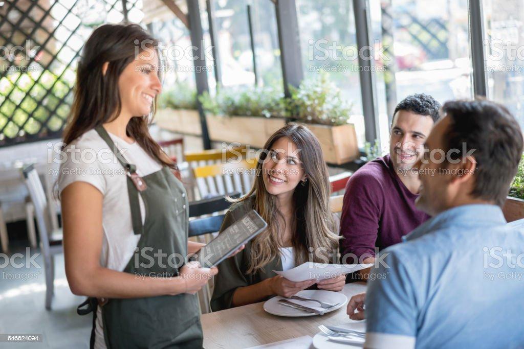 Serveerster serveren een groep vrienden in een restaurant foto