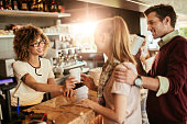 Close up photo of a waitress serving a young couple take-away coffee