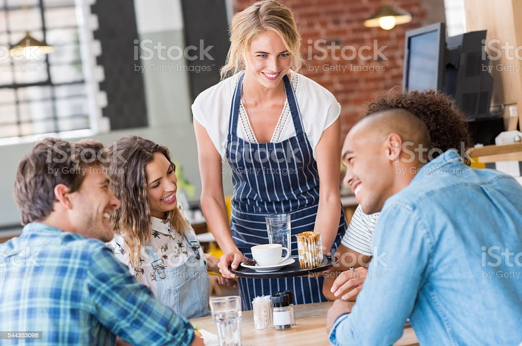 Waitress serving at table stock photo