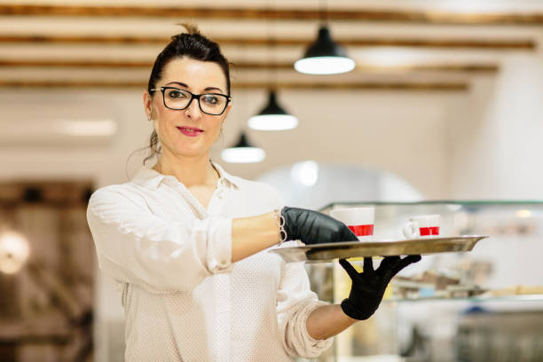 Waitress serving coffee inside her restaurant while looking at camera smiling.