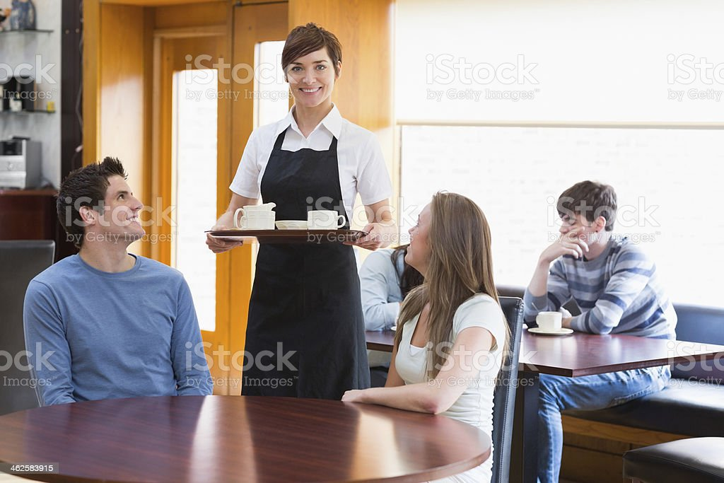 Waitress serving coffee to couple royalty-free stock photo