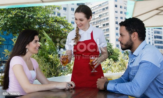635812444 istock photo Waitress serving cold beer to a love couple at restaurant 635780970