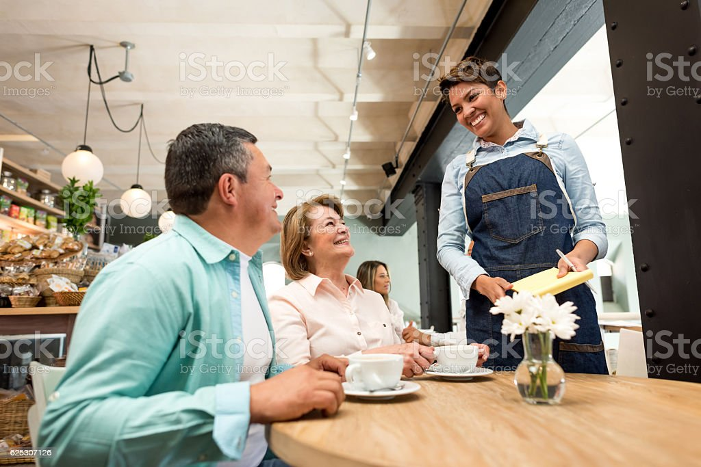 Waitress serving couple at a restaurant stock photo