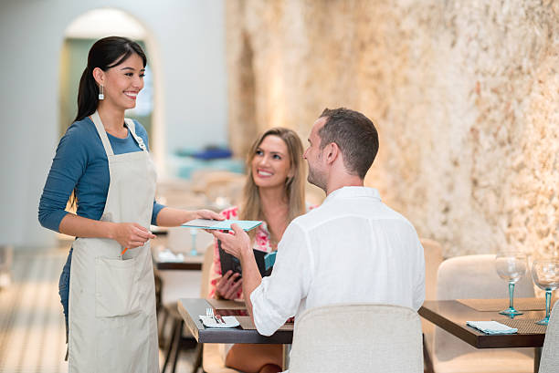waitress serving couple at a restaurant - being in a relationship with someone is going to require stock photos and pictures